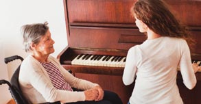 Elderly with woman at piano playing music